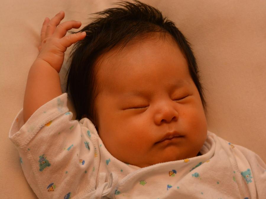 片手を上げて眠る赤ちゃん